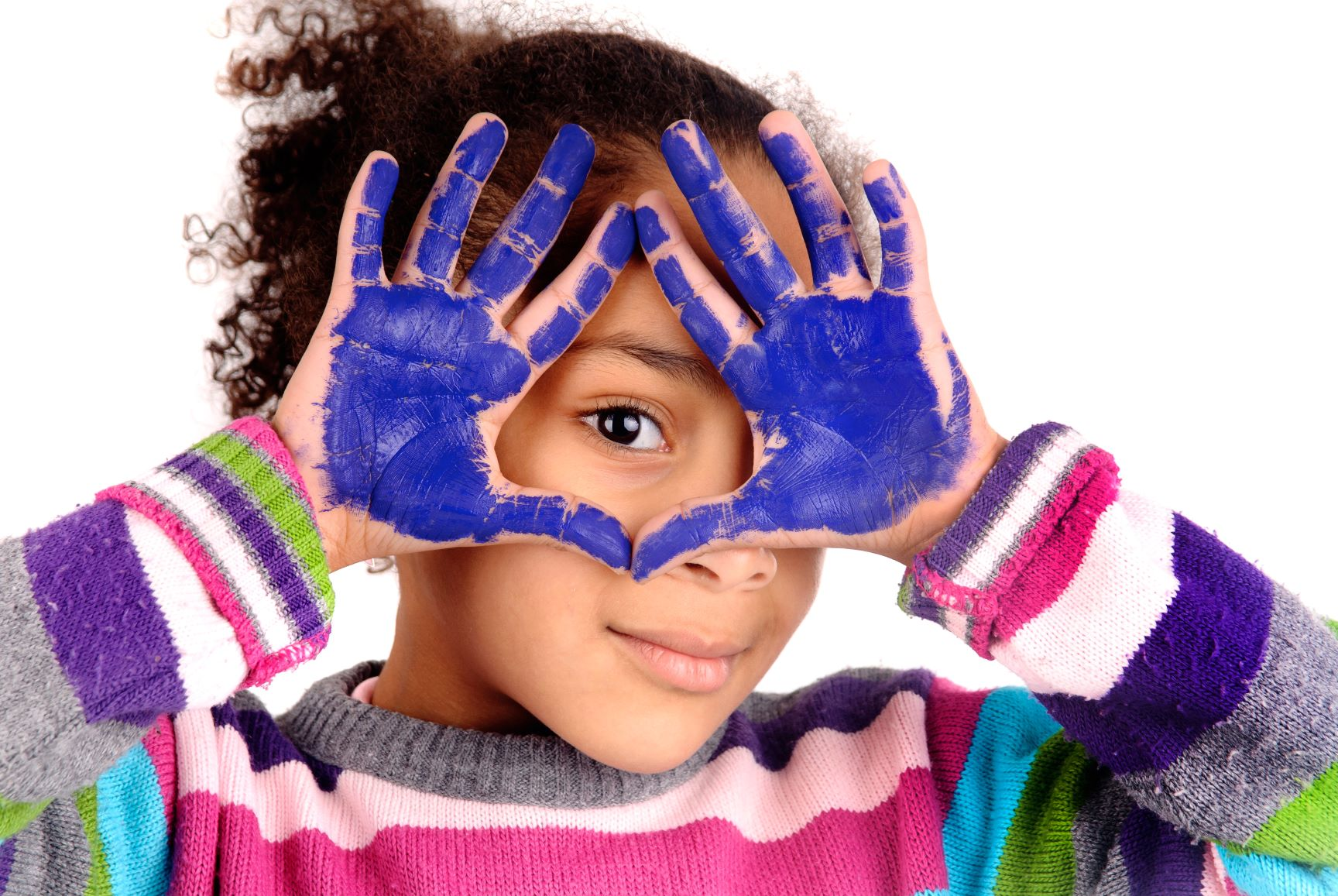 girl with colorful striped sweather and purple paint on her hands, looking through her hands with one eye