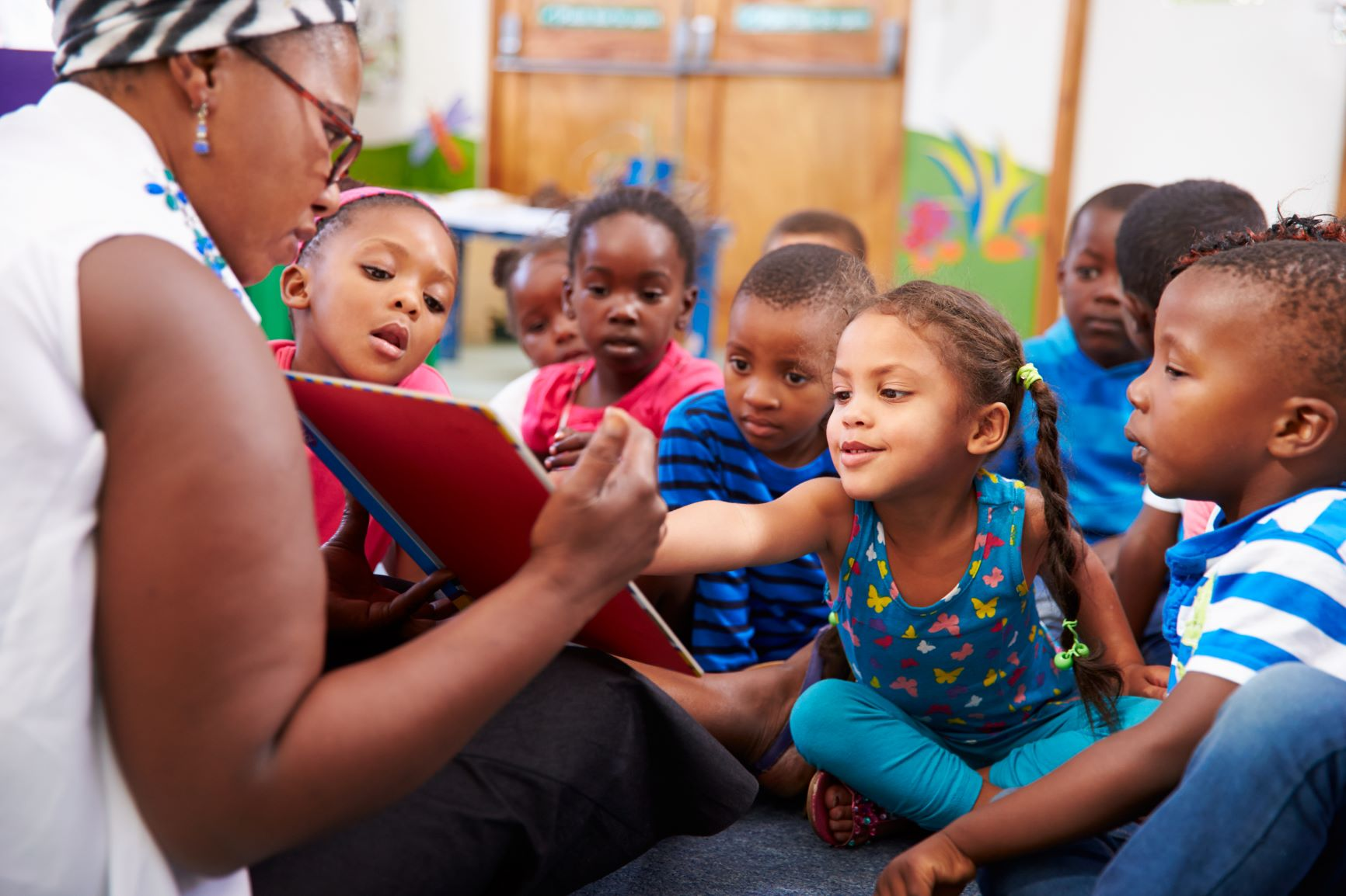 Preschool teacher reading to kids during story time, little girl pointing at book