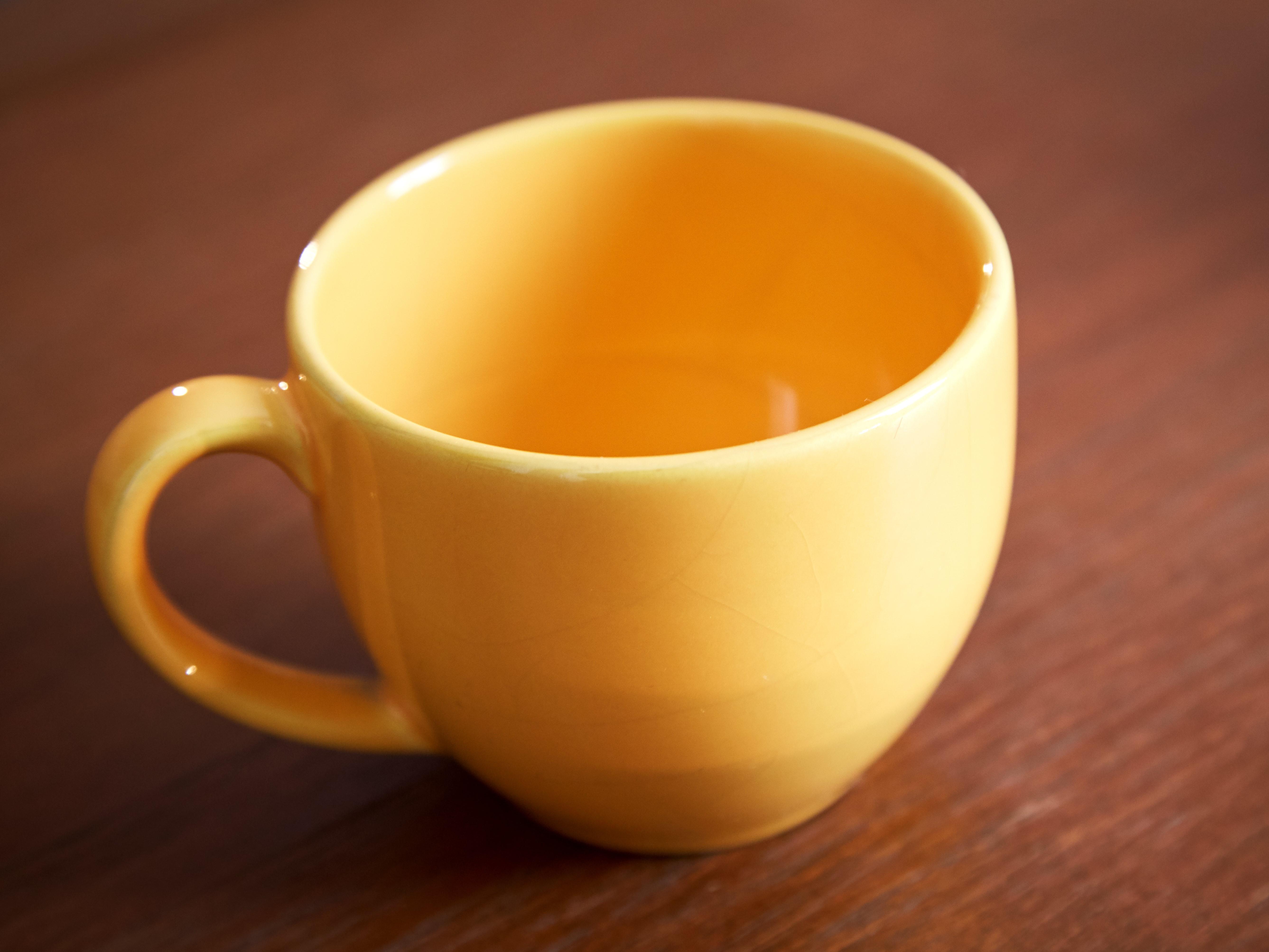 yellow ceramic mug on wood surface