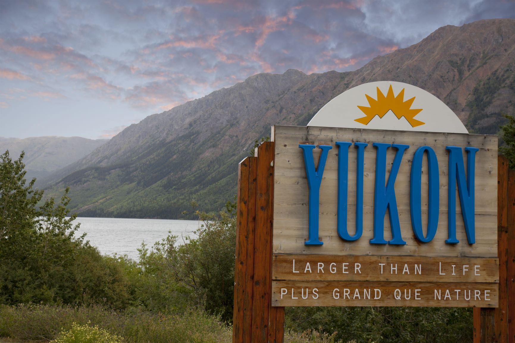 Yukon: Larger Than Life Sign with lake and mountains in background